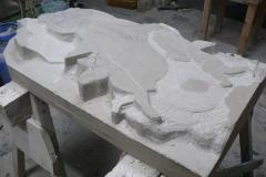 początek tworzenia płaskorzeźby w kamieniu, nagrobek z motywem Matki boskiej
